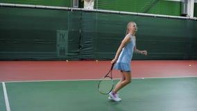 Nastolatek w sport smokingowe praktyki tenisowa gra w klubie sportowym dziewczyna bije piłki przez sieci z a zbiory