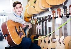 Nastolatek wybiera gitary akustyczne Zdjęcie Royalty Free