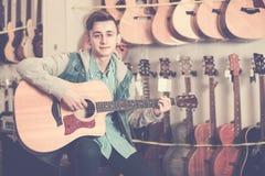 Nastolatek wybiera gitary akustyczne Obraz Stock