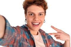 Nastolatek z kolczyk pracownianą pozycją odizolowywającą na białym bierze selfie w górę pokazywać pokoju znaka ono uśmie obraz royalty free