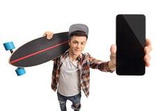 Nastolatek z longboard pokazuje telefon obrazy stock