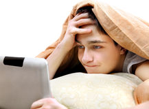 Nastolatek z pastylką w łóżku Obrazy Royalty Free