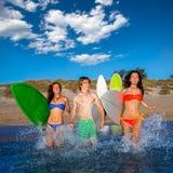 Nastolatków surfingowów bieg plaży grupowy chełbotanie Zdjęcia Royalty Free