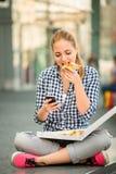 Nastolatka łasowania pizza patrzeje w telefonie Fotografia Royalty Free