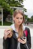 Nastolatka łasowania tort patrzeje w telefonie Fotografia Stock