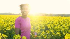 Nastolatka bieg i wody pitnej butelka w polu kolorów żółtych kwiaty przy zmierzchem zbiory