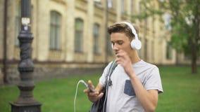 Nastolatka kładzenia hełmofony na i słuchać muzyka, audio app, playlista zbiory