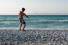 Nastolatka miotania kamienie w morze Obraz Royalty Free