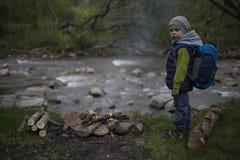 Nastolatka obsiadanie blisko ogienia w campingu i dopatrywania mapie Fotografia Stock