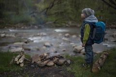 Nastolatka obsiadanie blisko ogienia w campingu i dopatrywania mapie Zdjęcia Stock