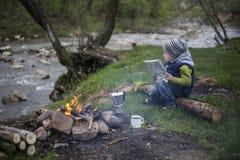 Nastolatka obsiadanie blisko ogienia w campingu i dopatrywania mapie Fotografia Royalty Free