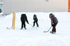 Nastolatkowie bawić się hokeja na domowym łyżwiarskim lodowisku Tyumen, Rosja Obraz Royalty Free