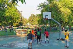 Nastolatkowie bawić się koszykówkę przy miasto parkiem zdjęcia royalty free