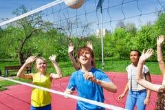 Nastolatkowie bawić się siatkówkę blisko sieci fotografia stock