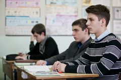 Nastolatkowie siedzi przy jeden słuchaniem i biurkiem ich nauczyciel zdjęcie stock