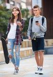 Nastolatkowie z jeździć na deskorolce outdoors Obraz Royalty Free