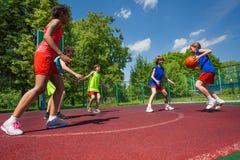 Nastolatkowie zespalają się bawić się mecz koszykówki wpólnie Obrazy Stock