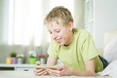 Nastoletni bawić się telefon Obrazy Stock