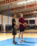 Nastoletni chłopacy trzyma koszykówkę na absztyfikują drużyny i dążenia pojęcia obrazy royalty free