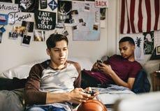 Nastoletni chłopacy wiszący w sypialni out fotografia stock