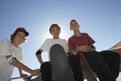 Nastoletni Chłopacy Z Jeździć na deskorolce Przeciw niebieskiemu niebu Obraz Stock