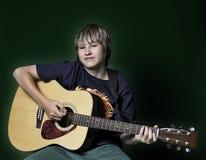 Nastoletni chłopak bawić się gitarę Zdjęcia Stock