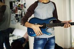 Nastoletni chłopak bawić się gitarę elektryczną w sypialni muzyki i hobby pojęciu zdjęcie royalty free