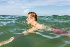 Nastoletni chłopak cieszy się dopłynięcie w oceanie obrazy royalty free