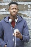 Nastoletni Chłopak Jest ubranym hełmofony I słuchanie muzyka W Miastowym S fotografia stock