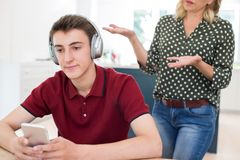 Nastoletni Chłopak Jest ubranym hełmofony I Używa telefon komórkowego Jest Nagg obrazy stock