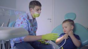 Nastoletni chłopak medyczna maska, rękawiczki i małe dziecko bawić się w dentysty biurze Młody facet uczy dzieciaka muśnięcie zdjęcie wideo