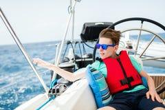 Nastoletni chłopak na pokładzie żeglowanie jachtu obrazy stock