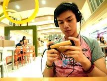 Nastoletni chłopak ogląda film na jego smartphone podczas gdy przy centrum handlowym w Antipolo mieście, Filipiny Obraz Stock