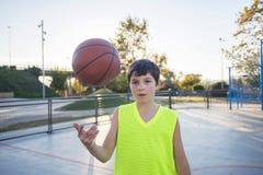 Nastoletni chłopak podrzuca koszykówkę od jeden ręki inny na a.c. obrazy royalty free