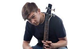 Nastoletni chłopak pokazuje szyi basową gitarę Fotografia Royalty Free