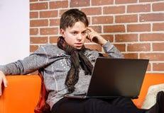 Nastoletni chłopak pracuje na laptopie Koncentracja i ochłonięcie obraz stock