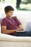 Nastoletni Chłopak Relaksuje Na kanapie Używa laptop W Domu fotografia stock
