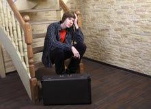 Nastoletni chłopak 14 roku, siedzi na drewnianych schodkach zbliża walizkę. fotografia stock