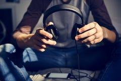 Nastoletni chłopak słucha muzyka przez jego smartphone w sypialni fotografia stock