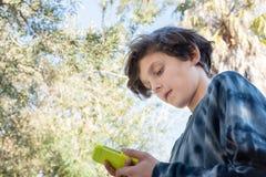 Nastoletni chłopak używa mądrze telefon fotografia stock