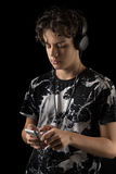 Nastoletni Chłopak Używa telefon z słuchawki, odizolowywającą na czerni Obrazy Stock