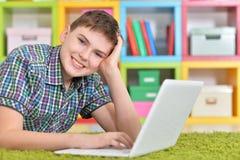 Nastoletni chłopak z laptopem zdjęcia stock