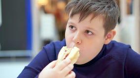 Nastoletni chłopiec łasowania hot dog w fast food kawiarni zbiory