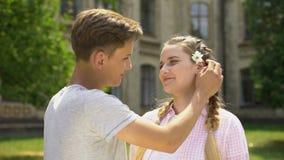 Nastoletni chłopiec kładzenia kwiat w dziewczyna włosy, pierwszy miłość, czysty związek zbiory