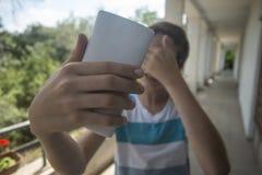 Nastoletni chłopak bierze selfie z jego telefonem zdjęcia stock