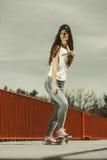 Nastoletni dziewczyny łyżwiarki jazdy deskorolka na ulicie Obraz Stock