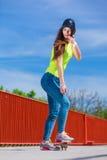 Nastoletni dziewczyny łyżwiarki jazdy deskorolka na ulicie Fotografia Stock