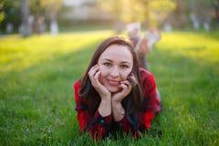 Nastoletni dziewczyny lying on the beach na trawie na słonecznym dniu i ono uśmiecha się, dziewczyna z rozwijać ciałem ono uśmiec fotografia royalty free