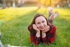 Nastoletni dziewczyny lying on the beach na trawie na s?onecznym dniu i ono u?miecha si?, dziewczyna z rozwija? cia?em ono u?miec zdjęcia stock