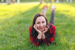 Nastoletni dziewczyny lying on the beach na trawie na s?onecznym dniu i ono u?miecha si?, dziewczyna z rozwija? cia?em ono u?miec fotografia stock